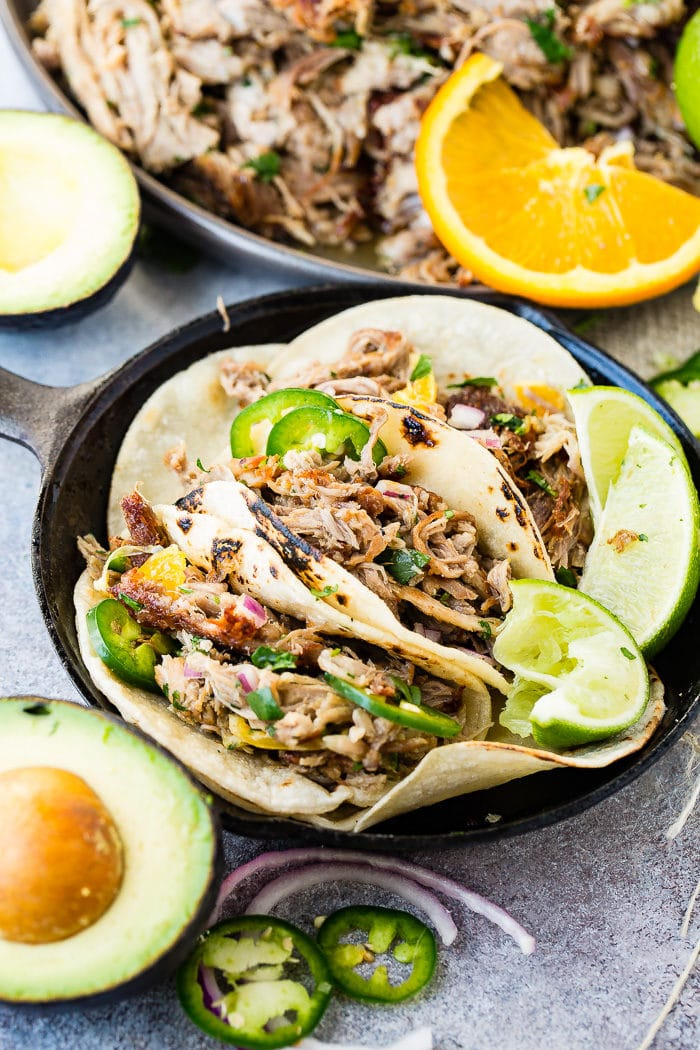 A photo of three pork carnitas tacos in a cast iron skillet topped with fresh jalapeno slices, diced red onions, and cilantro with a squeezed lime on the side.
