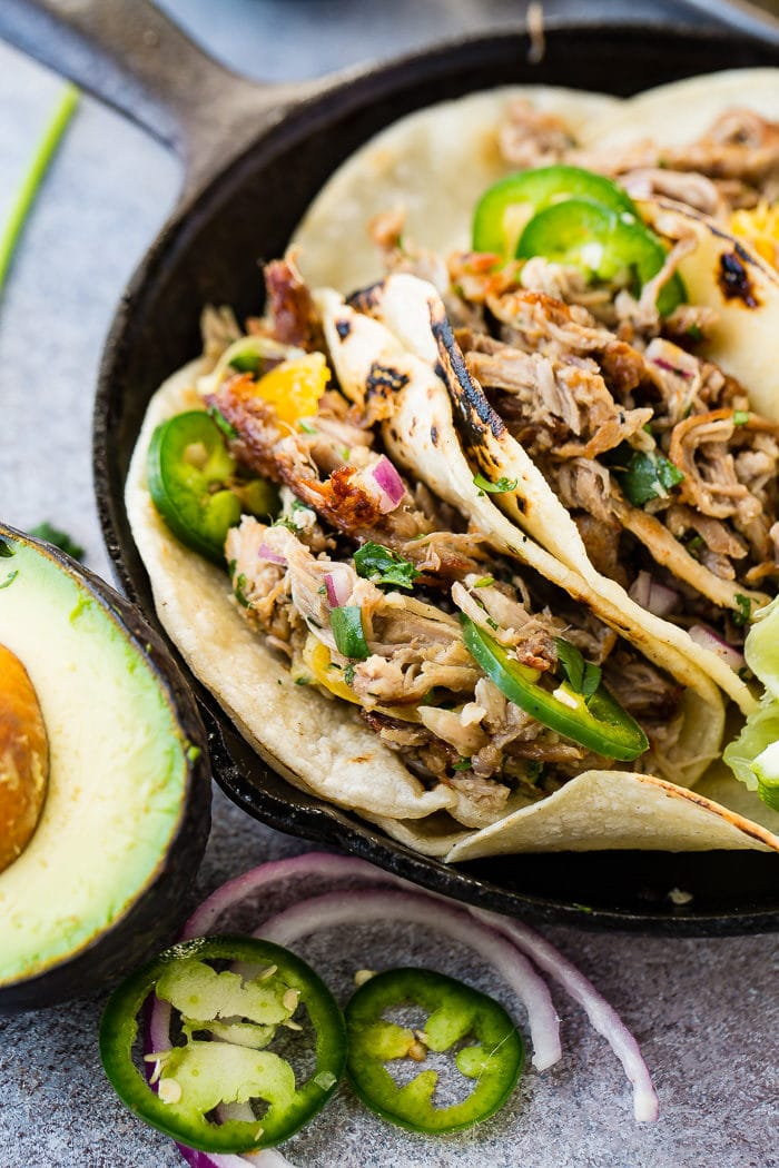 A photo of three pork carnitas tacos in a cast iron skillet topped with fresh jalapeno slices, diced red onions, and cilantro with a squeezed lime and a halved avocado on the side.