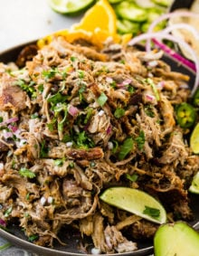 A photo of a mound of shredded pork carnitas on a dark gray plate and topped with fresh cilantro, red onions, slices of fresh jalapenos and lime wedges.