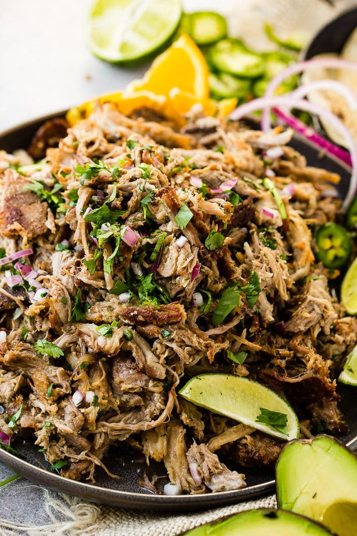 A photo of a mound of shredded pork carnitas in a cast iron skillet and topped with fresh cilantro, red onions, slices of fresh jalapenos and lime wedges.