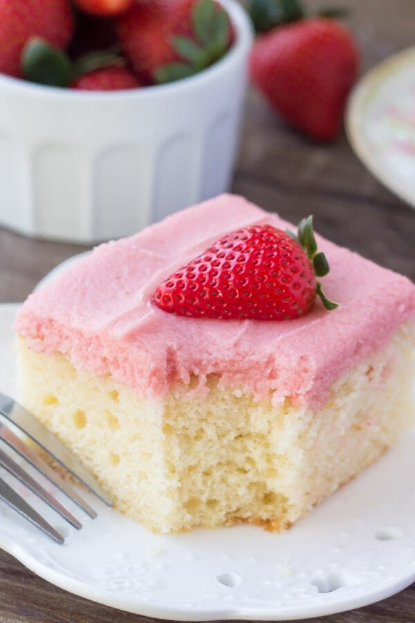 Soft, moist vanilla sheet cake topped with strawberry buttercream - you'll love the flavor combo and pretty pink color of this vanilla cake with fresh strawberry frosting.