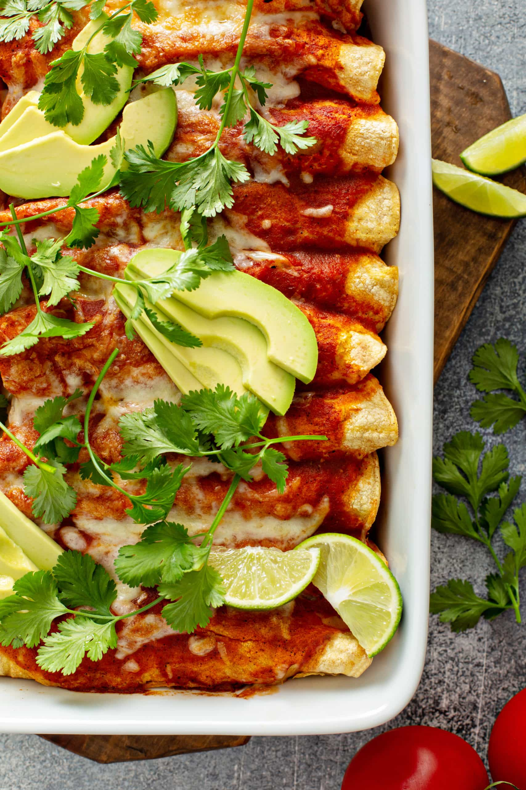A casserole dish full of enchiladas. They are topped with red enchilada sauce, sliced avocados, and cilantro leaves. There are lime wedges in the corners. and cilantro leaves on the table next to the casserole.