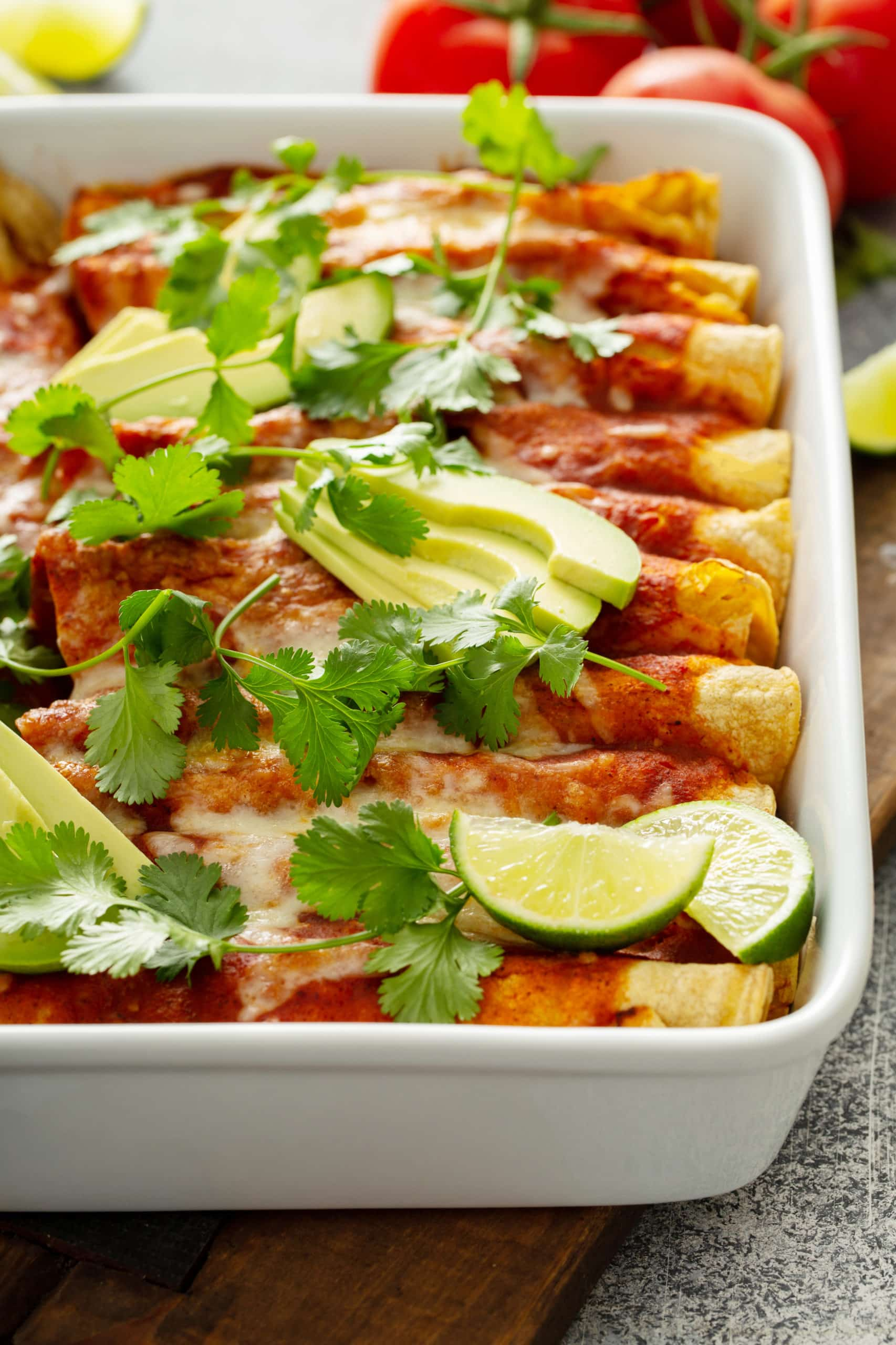 A casserole dish filled with enchiladas. They are topped with red sauce, sliced avocados, cilantro leaves and a few lime wedges in the corners.
