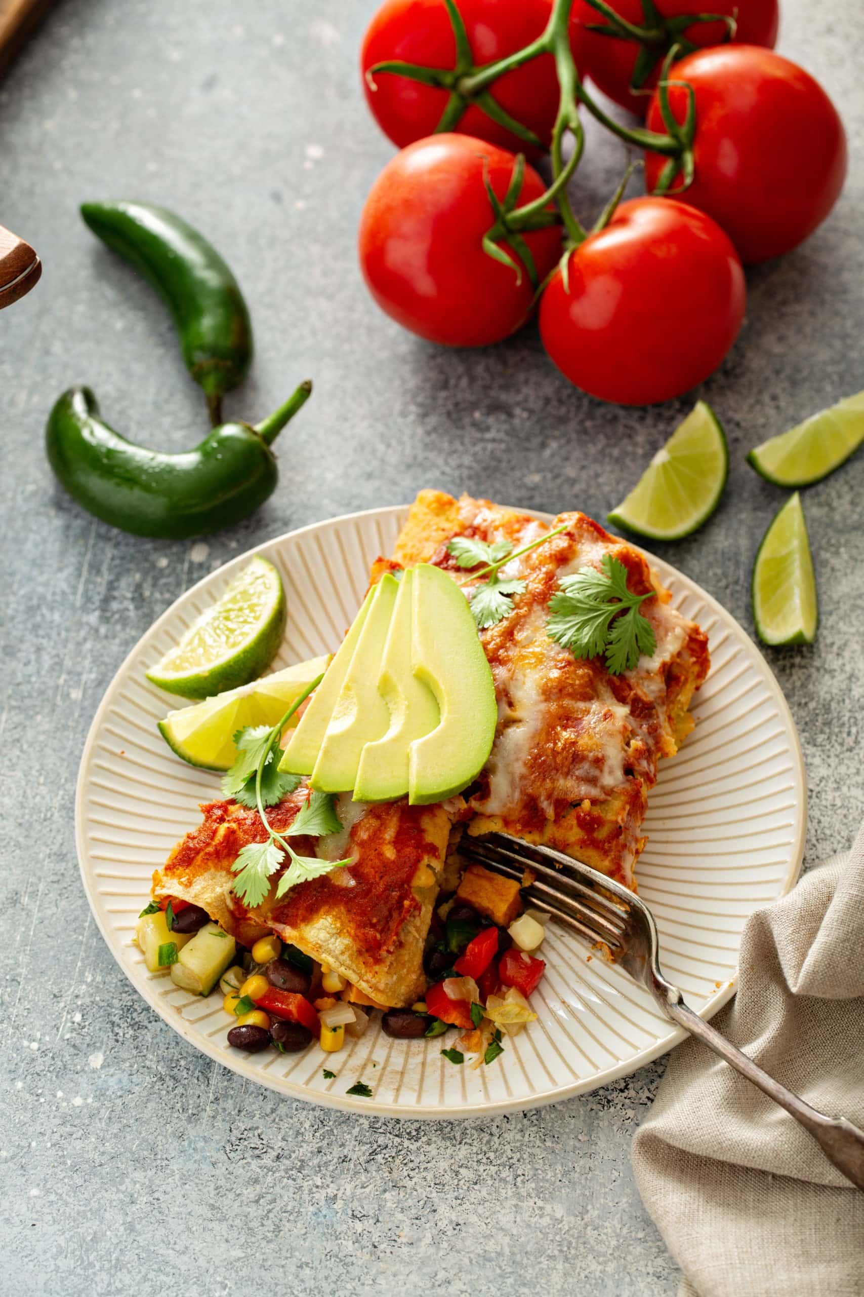Vegetarian enchiladas on a white dinner plate. They are topped with sliced avocados and cilantro leaves. There are some green chilies , lime wedges, and tomatoes in the background. There is a fork on the plate.
