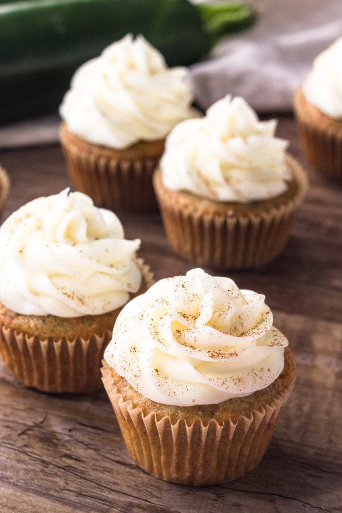 Zucchini cupcakes topped with cream cheese frosting and a sprinkle of cinnamon