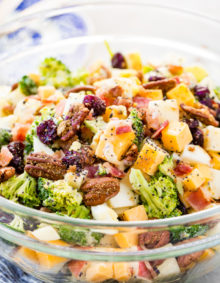 a glass bowl full of bacon, cheese, pepitas, craisins, broccoli, pecans and apples for the yummiest harvest cobb salad with poppy seed dressing