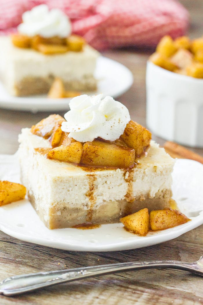 A slice of apple cheesecake bars topped with cinnamon sugar apples and whipped cream