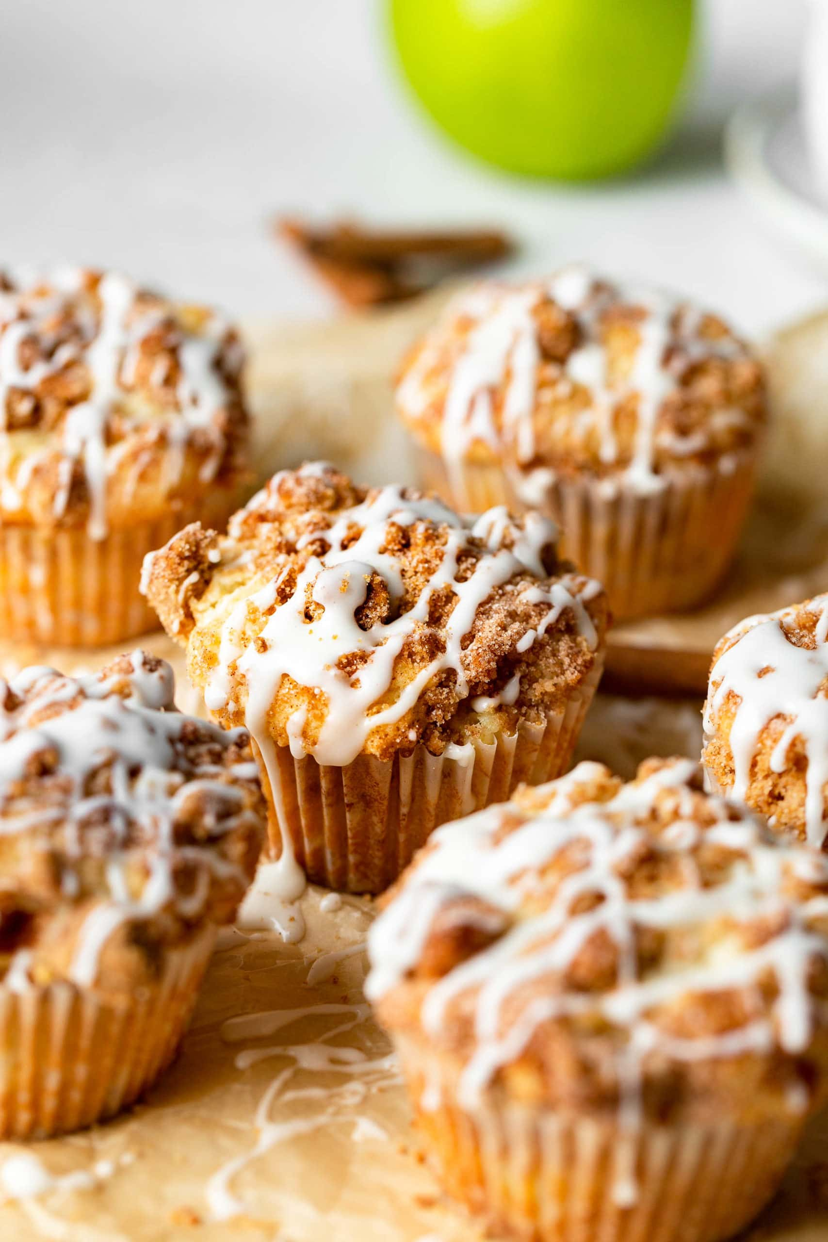a bunch of apple coffee cake muffins with streusel and icing sitting on natural parchment paper