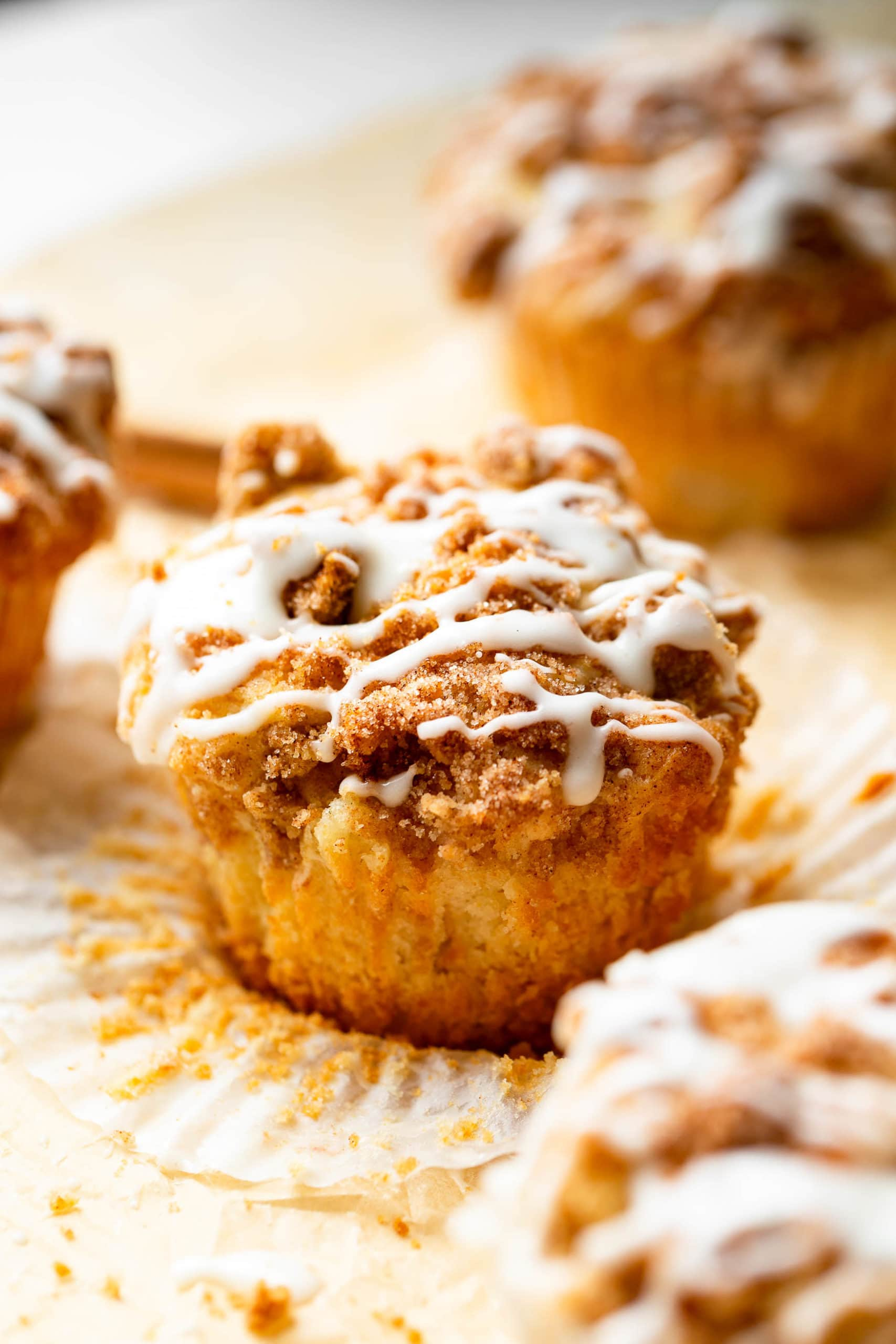 an apple coffee cake muffin sitting on an open paper liner with streusel and icing