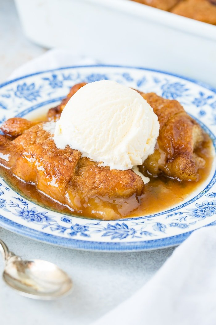 a blue china plate with two apple dumplings and caramel sauce with vanilla ice cream on top