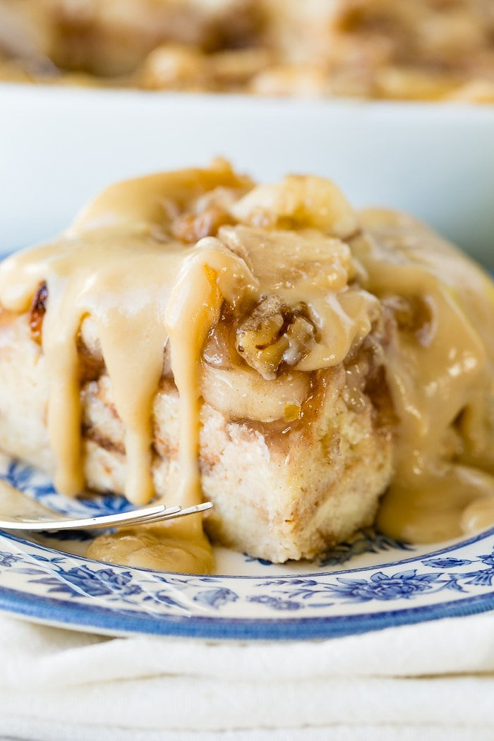 a large slice of apple bread pudding with vanilla sauce sitting on a blue china plate