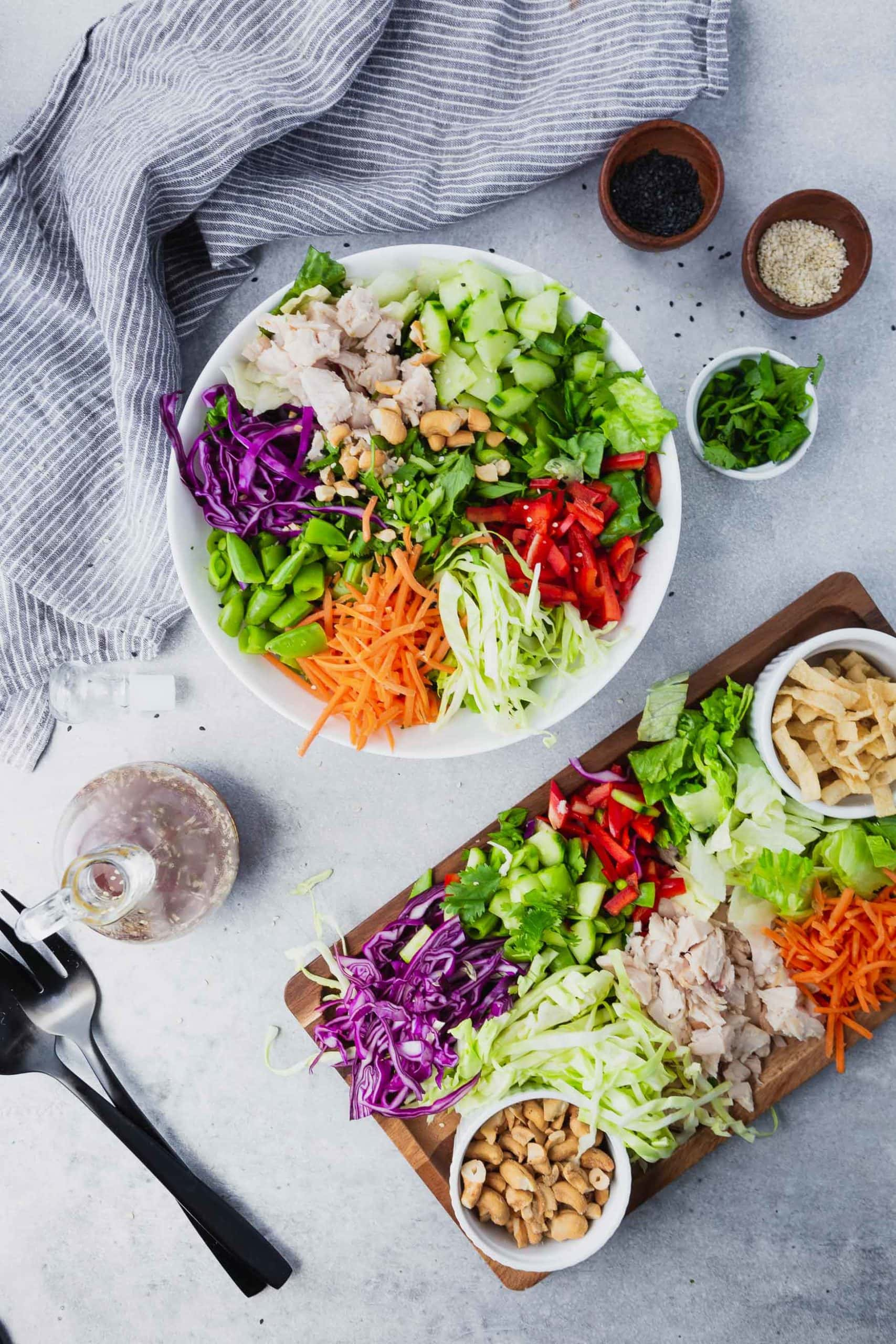 Picture all ingredients for Chinese chicken salad all in a large white bowl and also on a rectangular serving plate.
