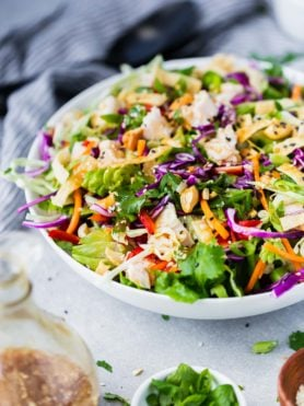 a photo of chinese chicken salad in a large white bowl.