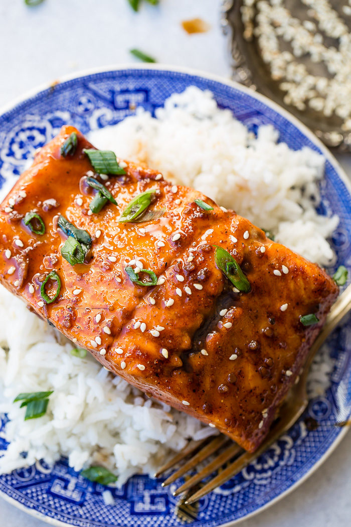 A glazed fillet of salmon with green onions and sesame seeds sitting on a bed of white rice on a blue Asian printed china dish.
