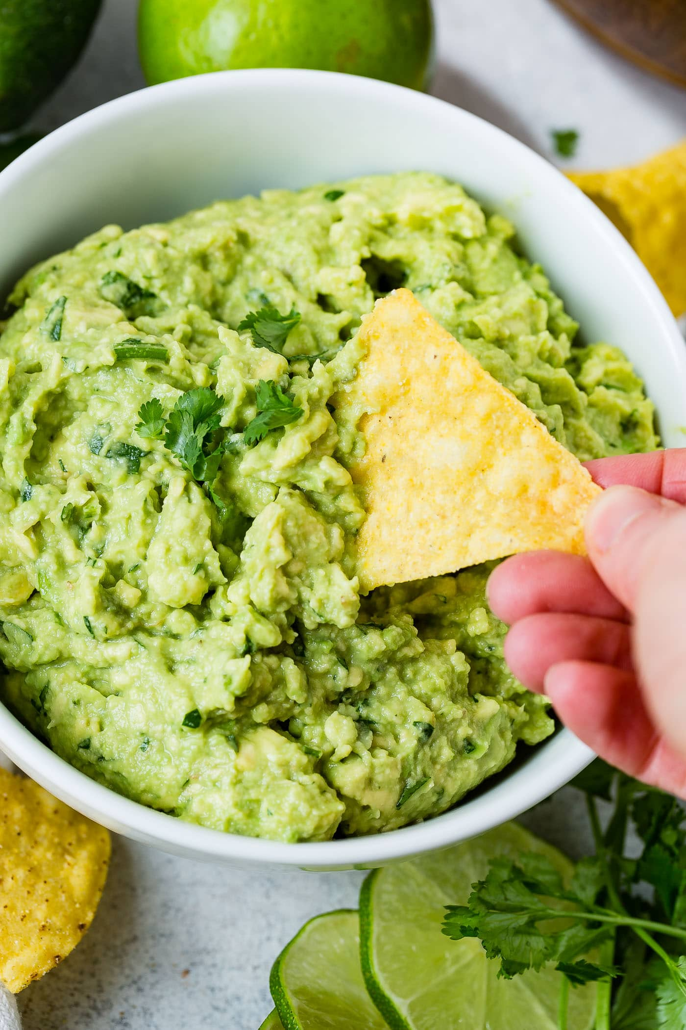 A tortilla chip being dipped into a bowl of fresh green guacamole. There are a couple of cilantro leaves on top of the guacamole.