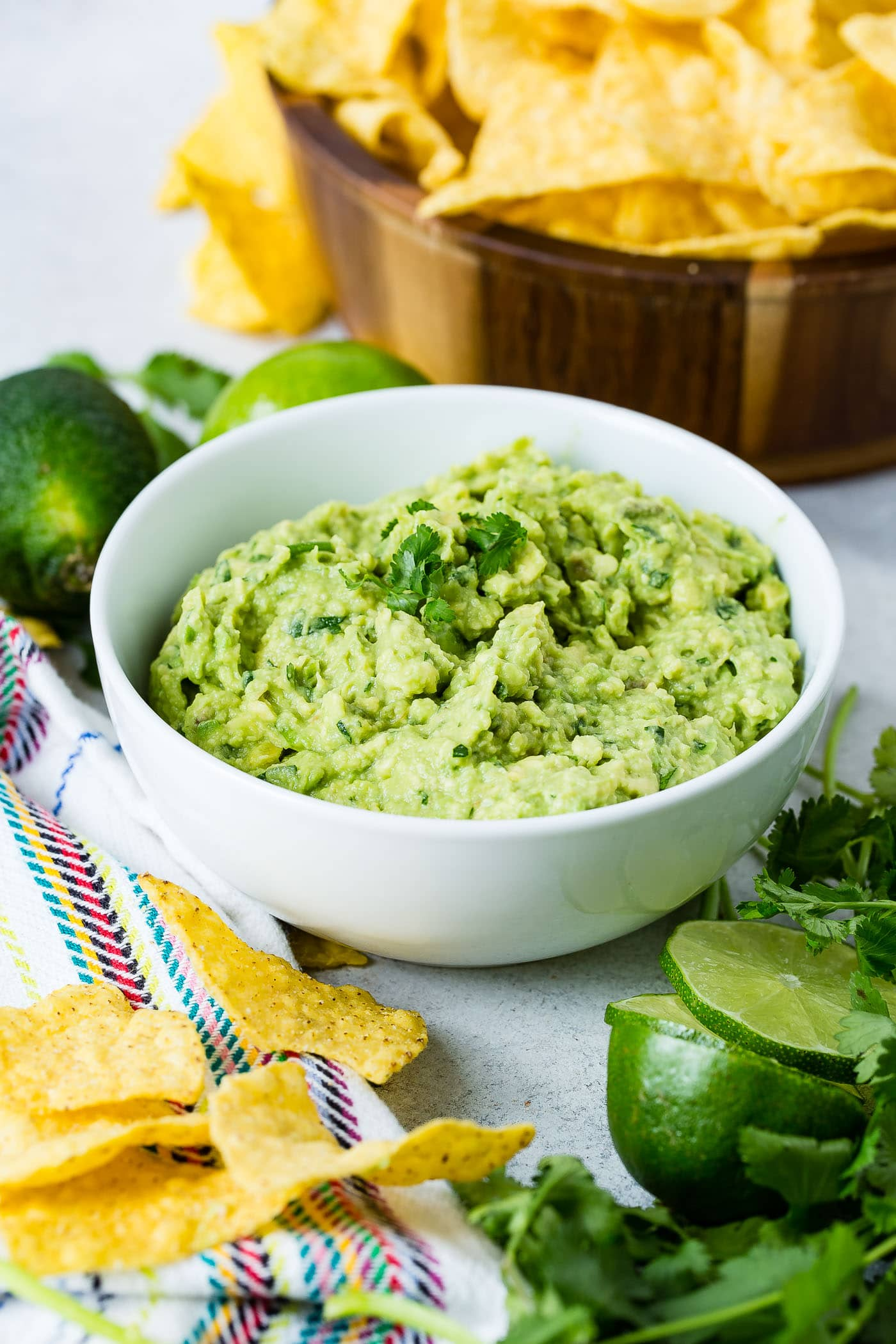 A bowl of fresh guacamole with a few cilantro leaves on top. There are tortilla chips scattered on the table in front of the bowl and a partially sliced lime next to the chips. There are two whole lime and a wooden bowl of tortilla chips in the background.