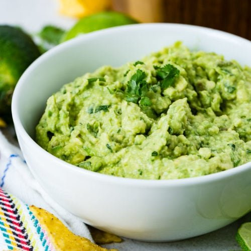 A white bowl of fresh guacamole with cilantro leaves on top. There are two whole limes and a wooden bowl of tortilla chips in the background. There are some more chips and slices of lime in front of the bowl.