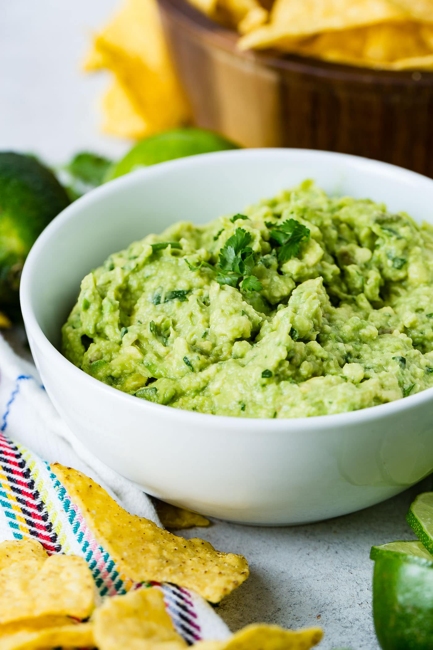 A white bowl of fresh guacamole with cilantro leaves on top. There are two whole limes and a wooden bowl of tortilla chips in the background.
