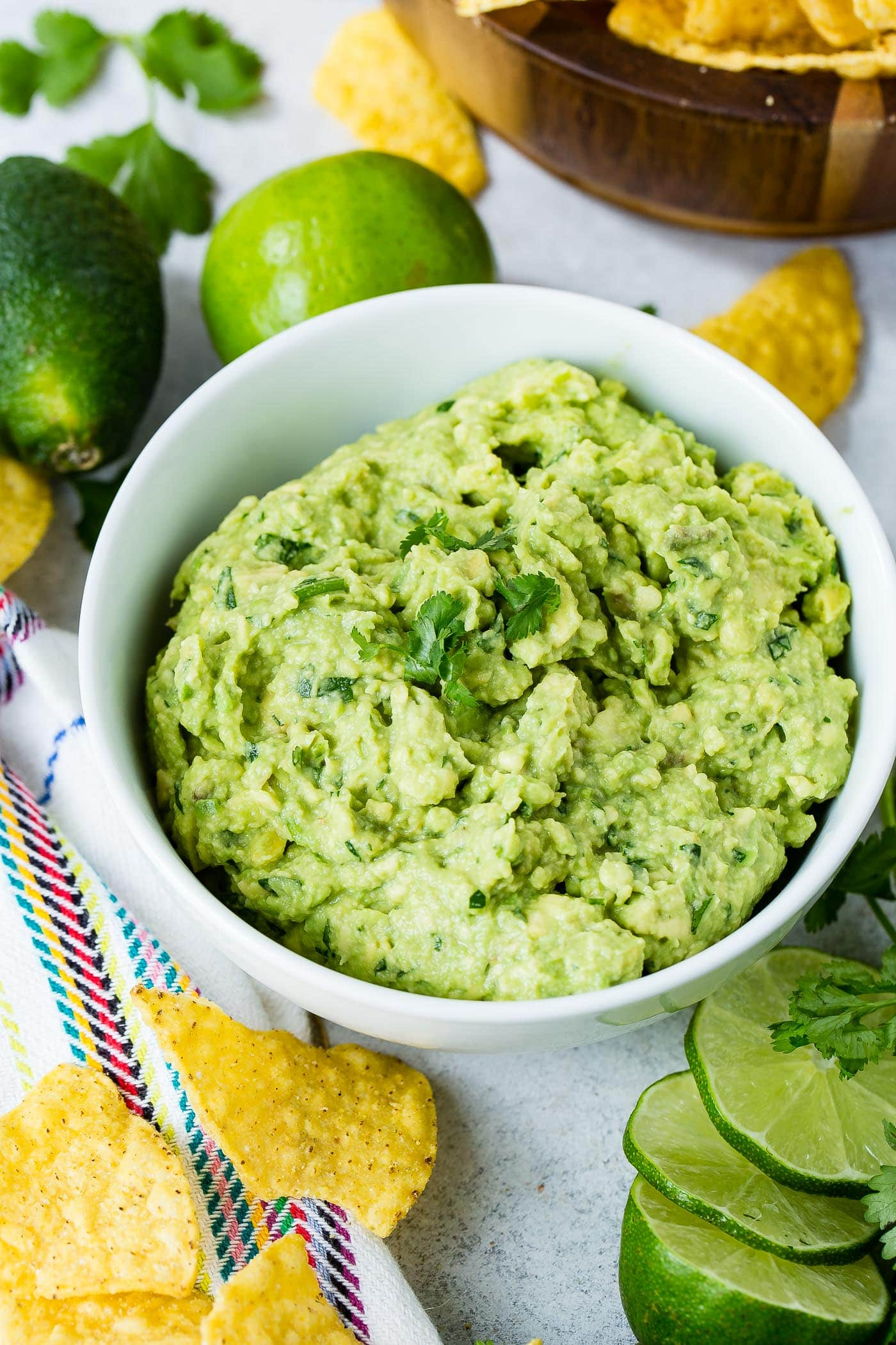 A bowl of homemade authentic guacamole with a few cilantro leaves on top. there are two whole limes and tortilla chips in the background and three slices of lime and more chips in front of the bowl.