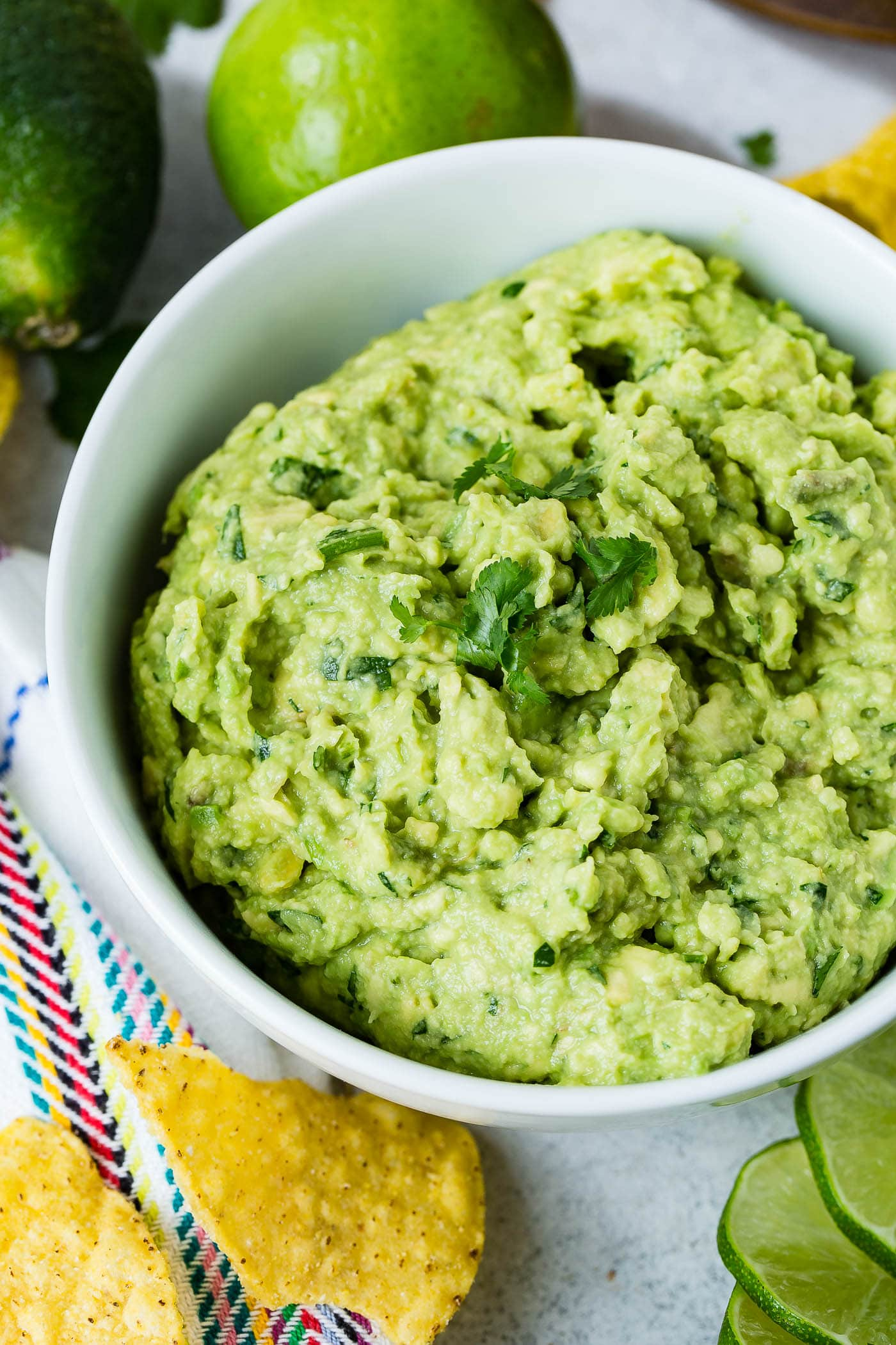 A white bowl of fresh guacamole. You can see the cilantro in the guacamole and a few cilantro leaves are on top. There are a few chips on the table next to the bowl.