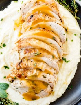 a photo of sliced turkey breast drizzled with gravy and garnished with fresh herbs on a bed of mashed potatoes all on a black plate