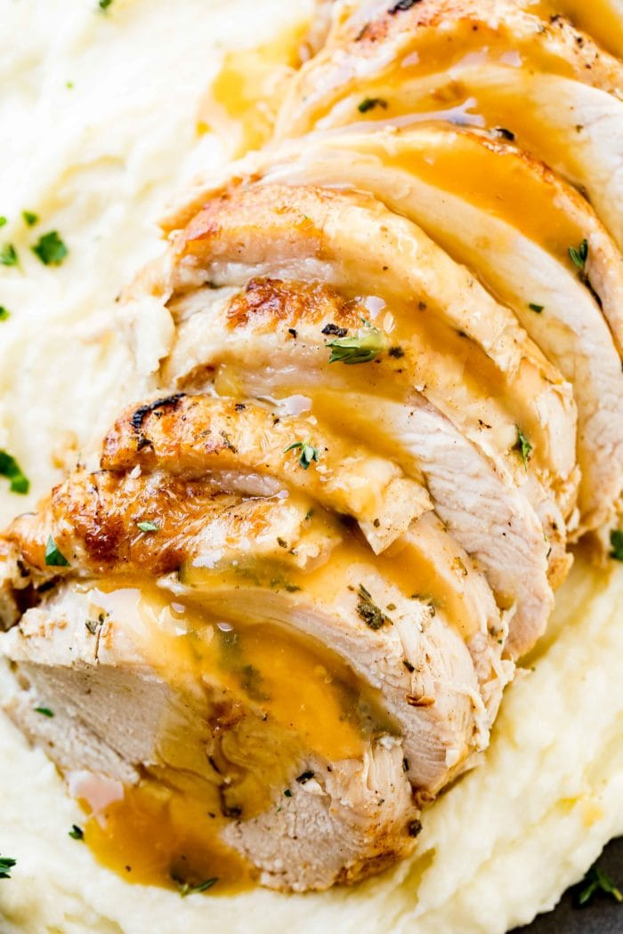 a photo of sliced instant pot turkey breast drizzled with gravy and garnished with fresh herbs on a bed of mashed potatoes