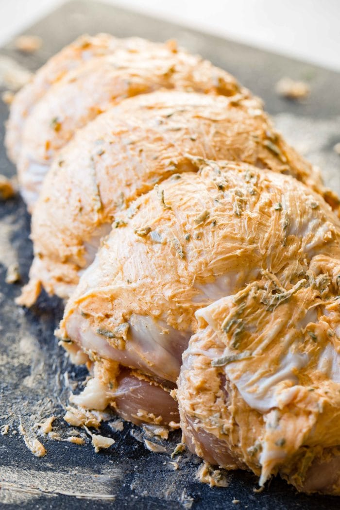 a photo of a raw turkey breast bound with twine and lathered in butter and fresh herbs
