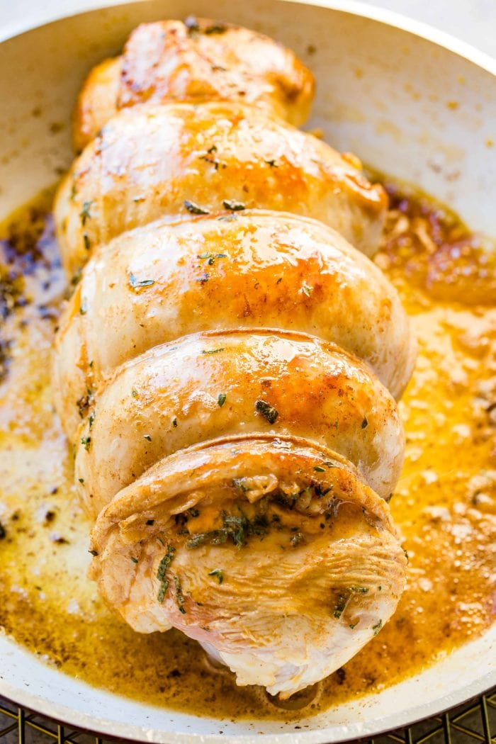a photo of a cooked turkey breast bound with twine in an Instant Pot sitting on top of all the juices that have cooked off