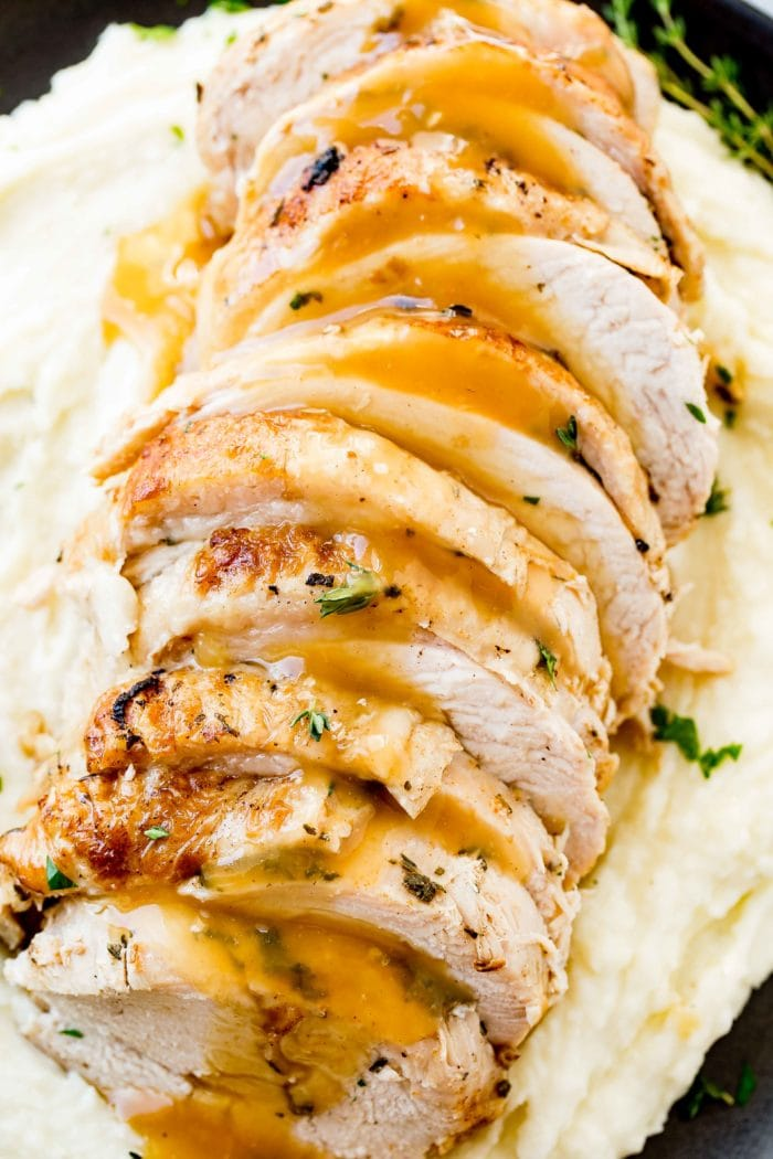 a photo of sliced turkey breast drizzled with gravy and garnished with fresh herbs on a bed of mashed potatoes
