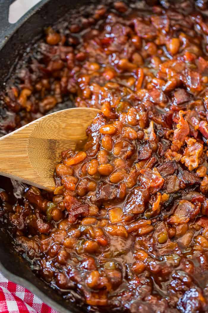 A cast iron skillet with saucy baked beans and a wooden spoon