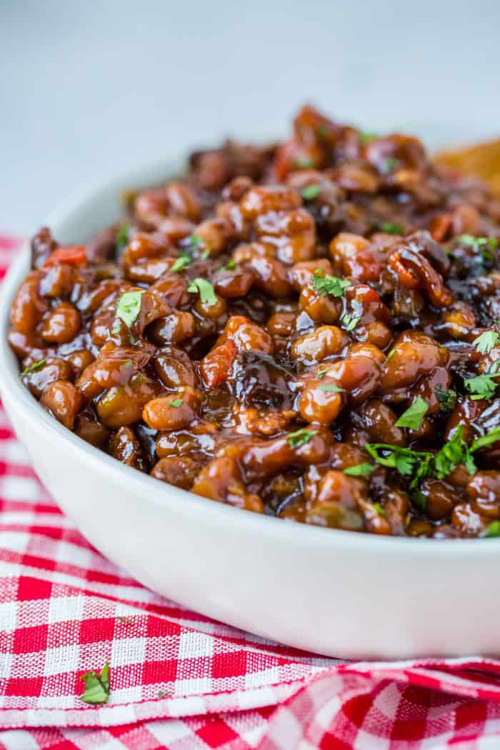 A white bowl full of saucy baked beans with chopped cilantro sitting on a red checkered napkin