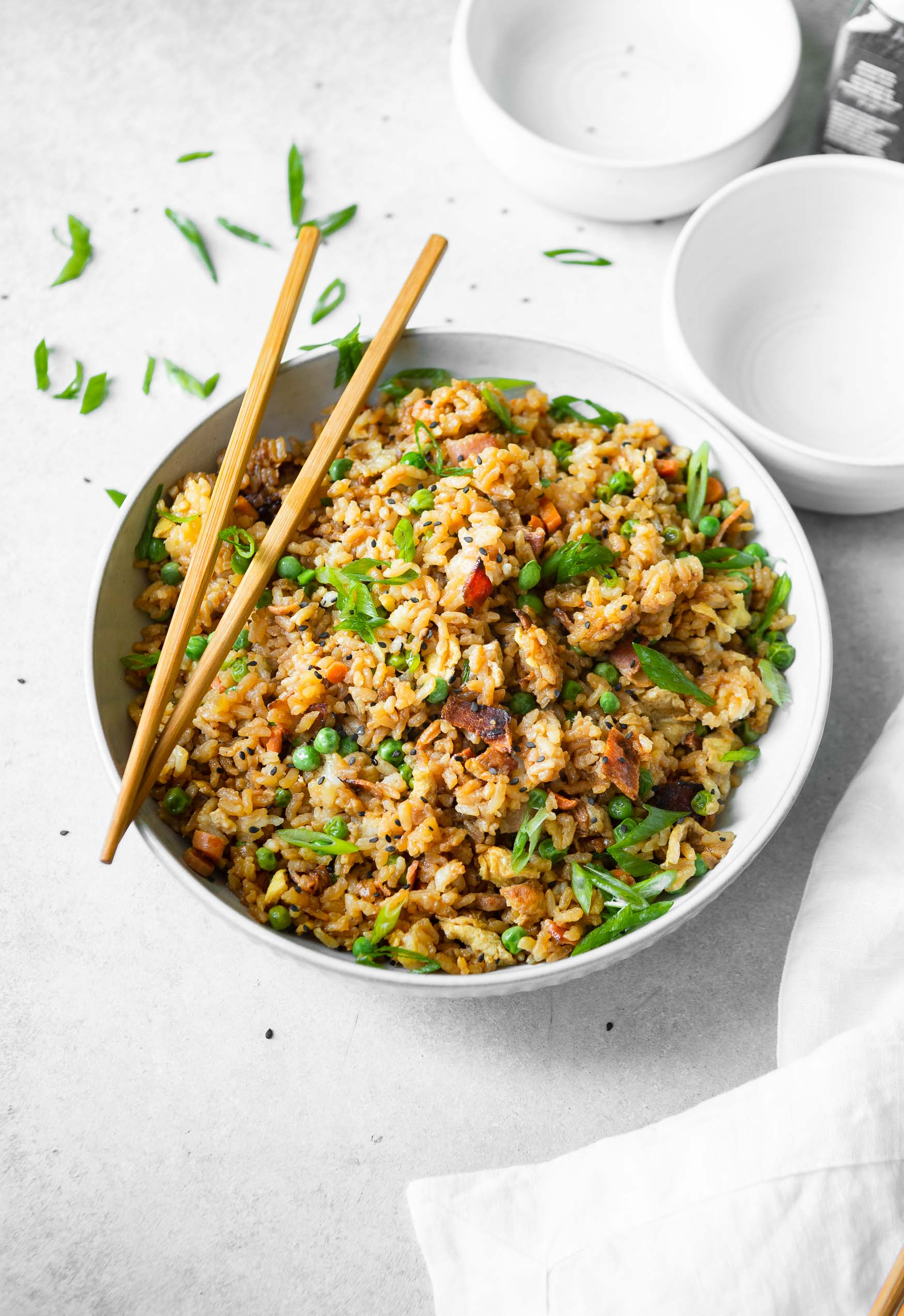 a bowl of fried rice with bacon, carrots and peas in a large white bowl with a pair of chopsticks resting on the side of the bowl.