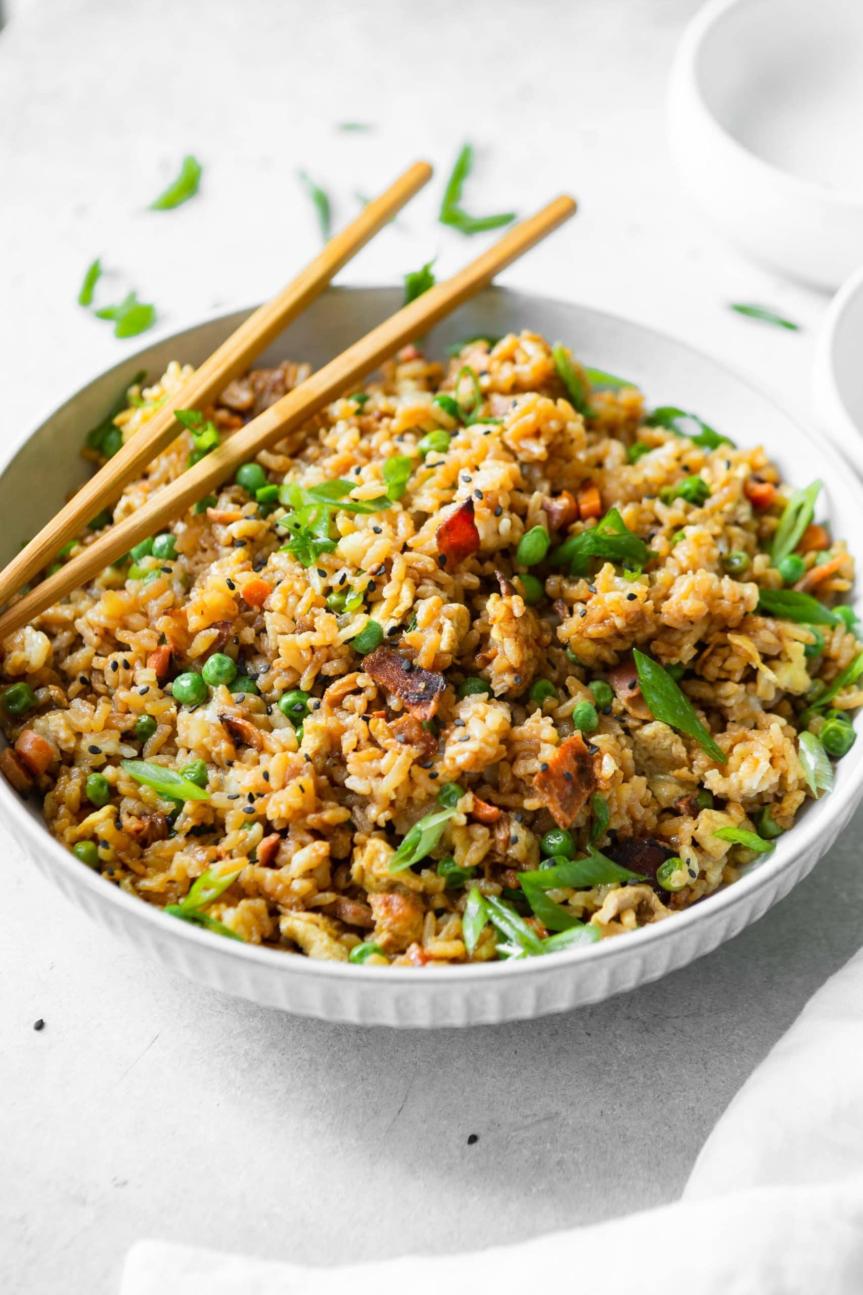 a large bowl of bacon fried rice with carrots, peas and chopsticks for fun!