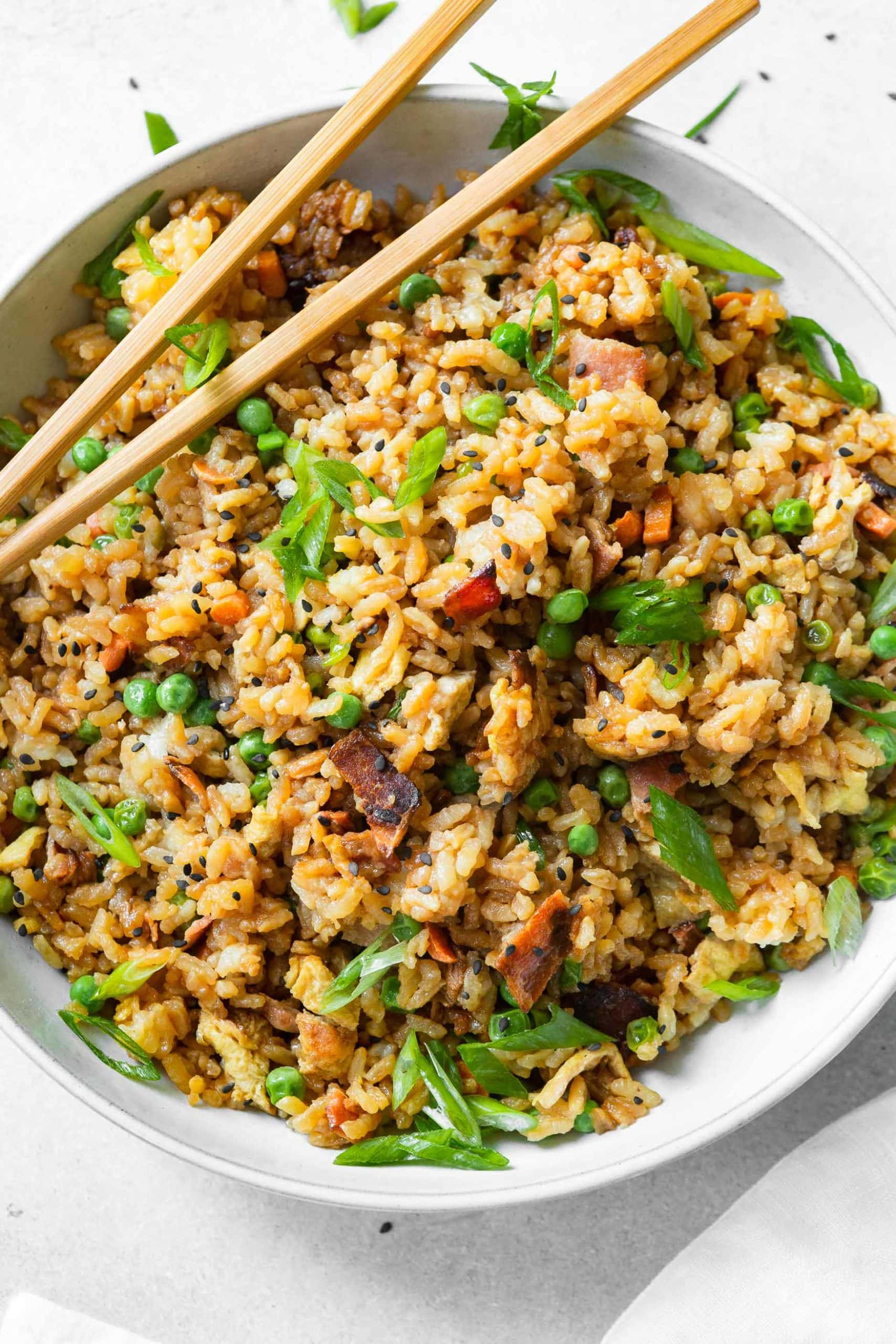 a bowl of bacon fried rice topped with sliced green onion and a pair of chopsticks on resting on the side of the bowl.
