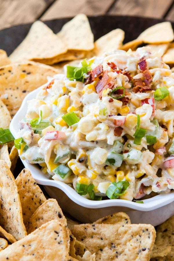close up of corn and bacon ranch dip in white dish with tortilla chips