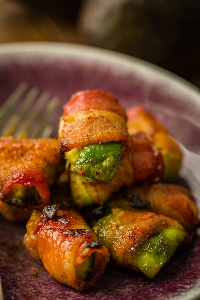 Bacon wrapped around pieces of green avocados with brown sugar and baked until crispy, all piled up on a plate as an easy appetizer recipe
