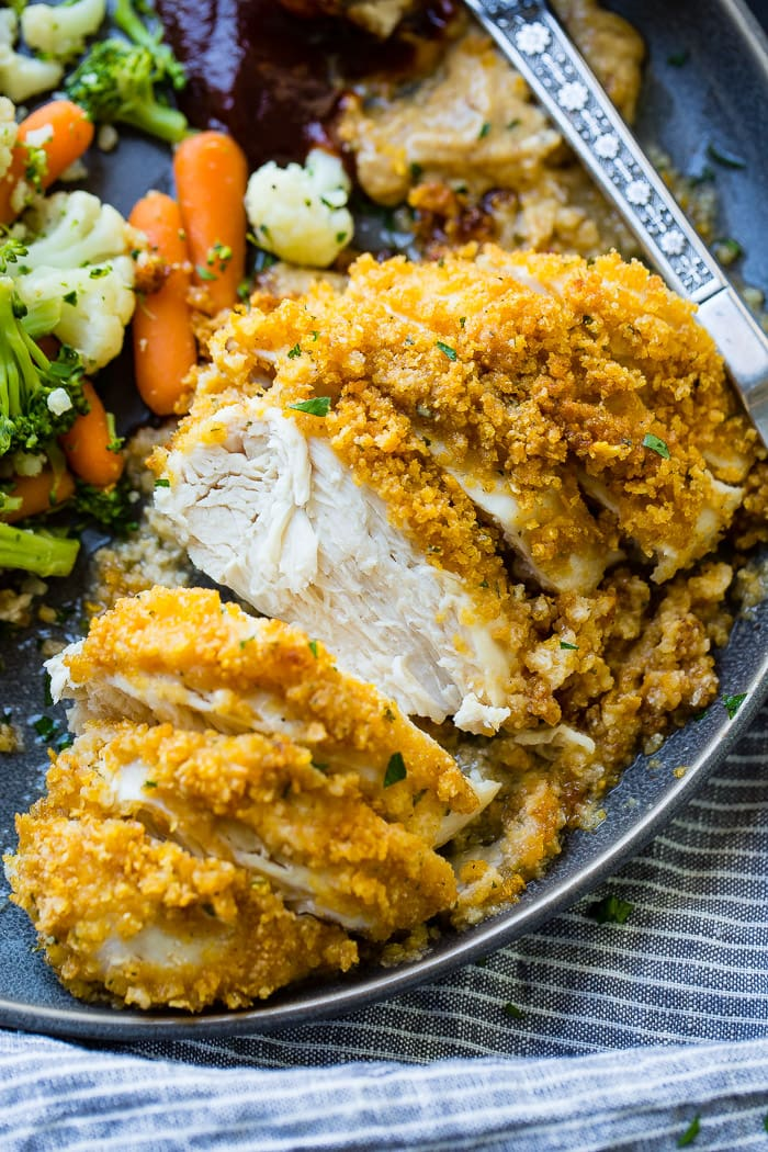 a grey plate full of steamed veggies and golden, baked quick and easy cornflake chicken recipe which has been sliced into pieces of chicken