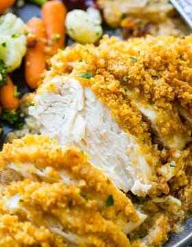 a grey plate full of steamed veggies and golden, baked quick and easy cornflake ranch chicken recipe which has been sliced into pieces of chicken