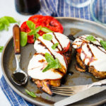 balsamic chicken with tomatoes and mozzarella over the top and a sprinkle of basil