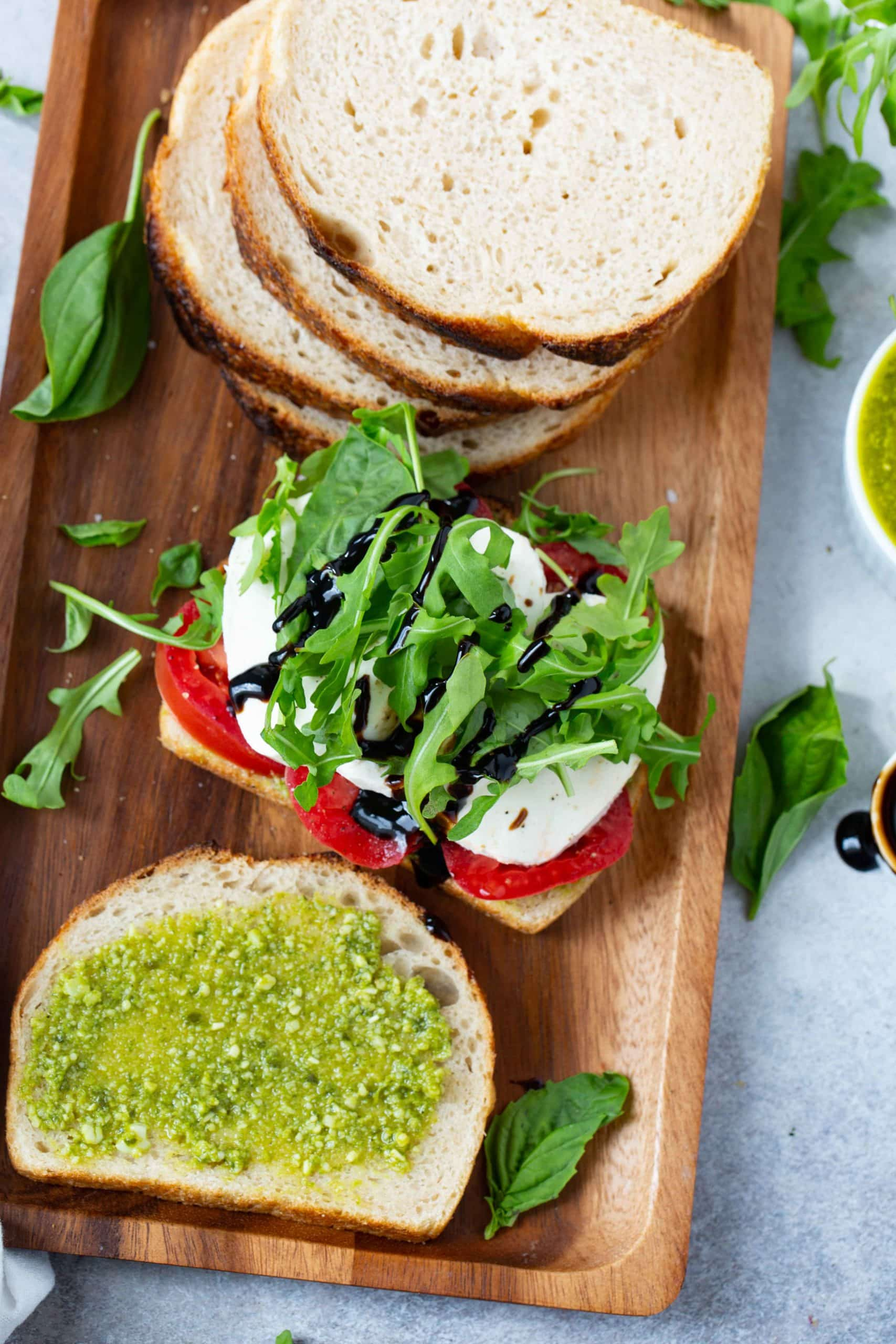 A wooden tray with sliced bread, a slice of bread with tomatoes, mozzarella cheese, and arugula on top. There is another slice of bread laying next to it that has been spread with pesto. Arugula and basil leaves lay on the tray and table next to the tray.
