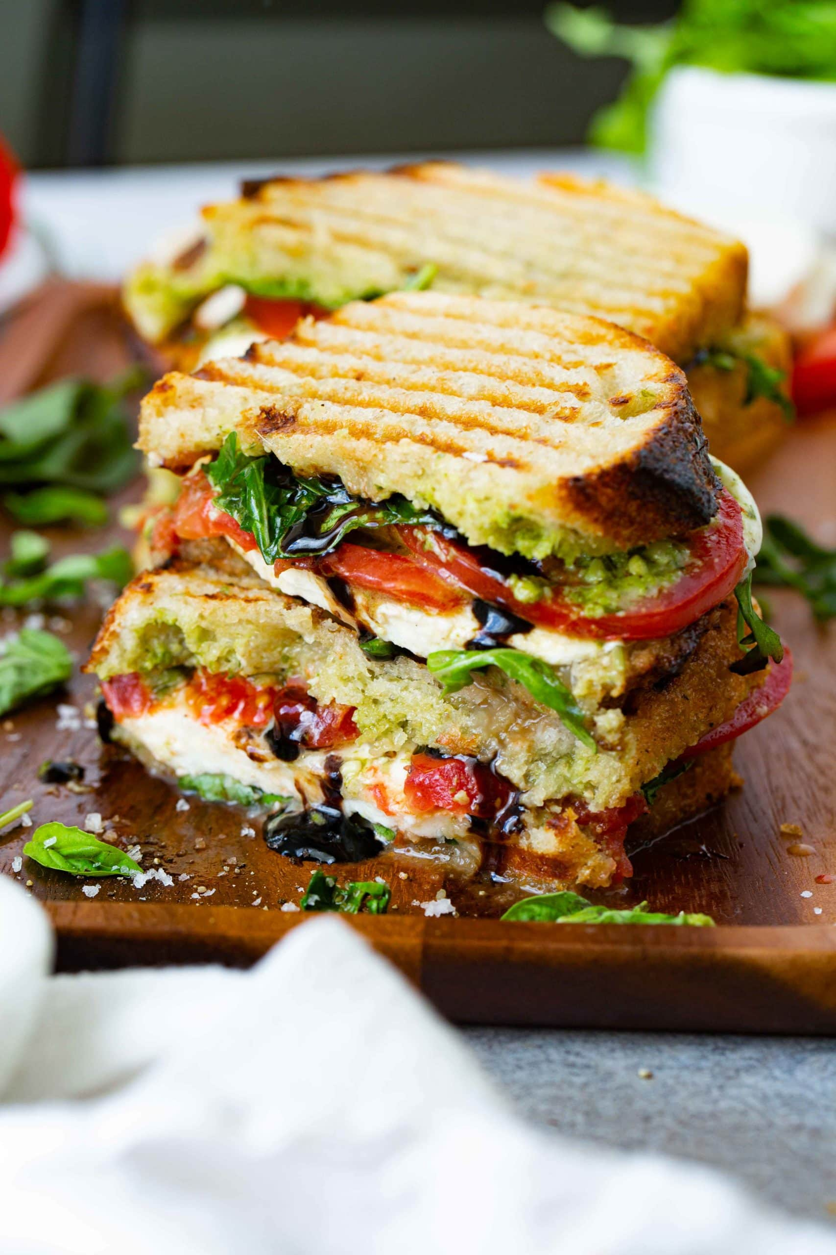 A grilled caprese panini that has been cut in half and stacked on top of each other. You can see the grill marks on the bread and the arugula, tomatoes, pesto and mozzarella cheese inside. A little balsamic glaze is oozing from the sandwich. There is another sandwich in the background, and some arugula and basil on the table.