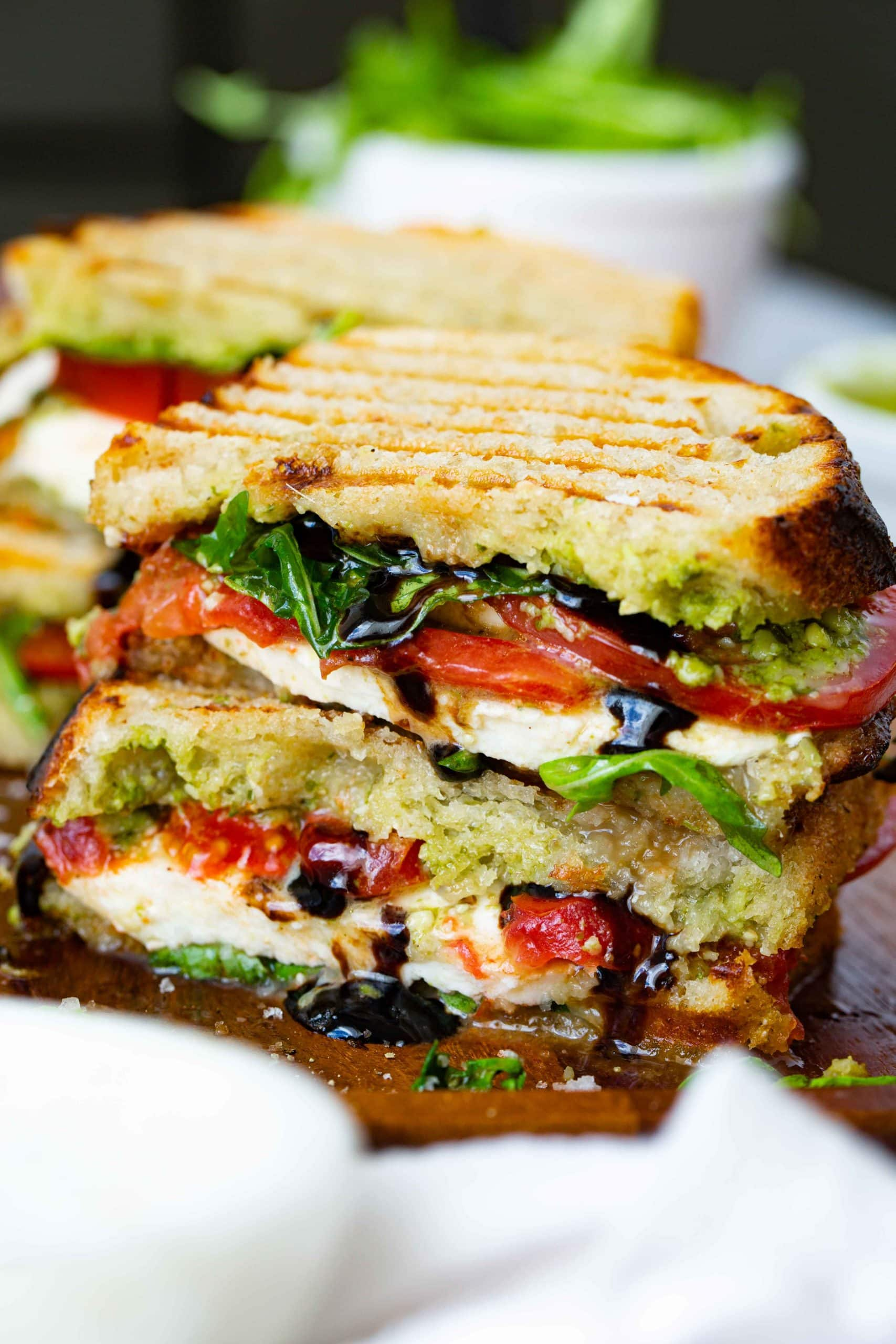 A balsamic glazed caprese sandwich that has been cut in half and stacked on top of each other. The sandwich has grill marks on top and has arugula, fresh mozzarella cheese slices and tomato slices inside. You can see the balsamic glaze dribbling out of the sandwich and another sandwich in the background.