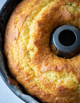 A dark bundt pan with a beautiful, bright yellow banana pudding bundt cake