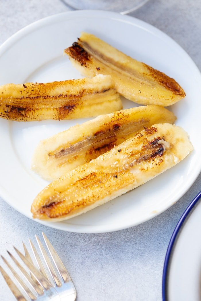 a white plate with halved bananas that have been caramelized in butter on a hot skillet