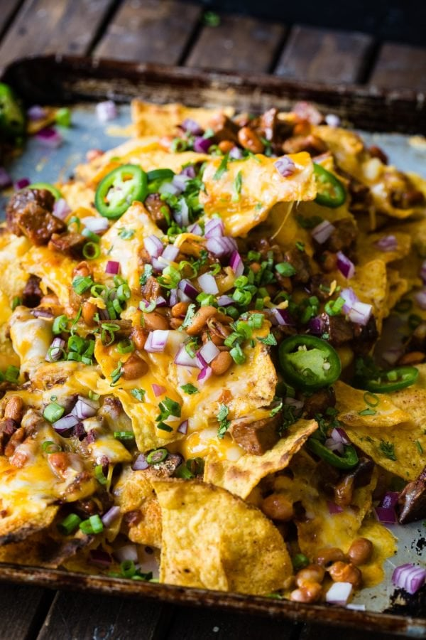 A photo of bbq brisket nachos with melted cheese all over the top and sliced jalapenos, diced red onion and fresh chopped cilantro.