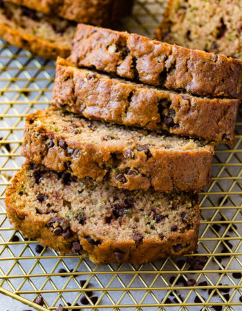 a photo of slices of chocolate chip zucchini bread tipped over on top of each other on top of a gold wire cooling rack