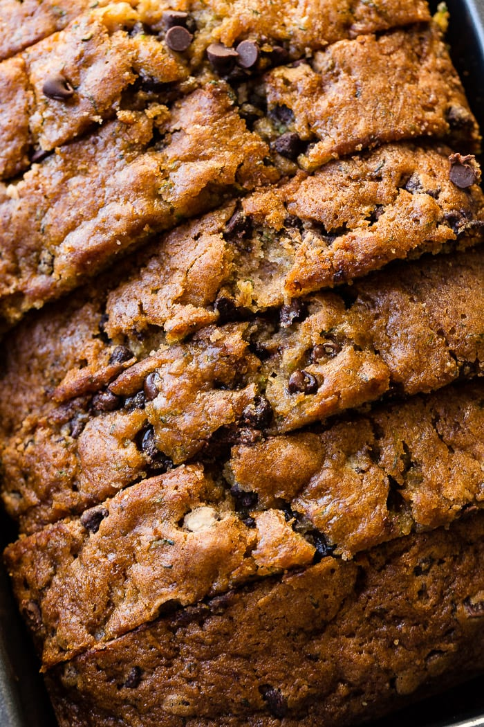 an overhead picture of a loaf of sliced chocolate chip zucchini bread still in the bread pan
