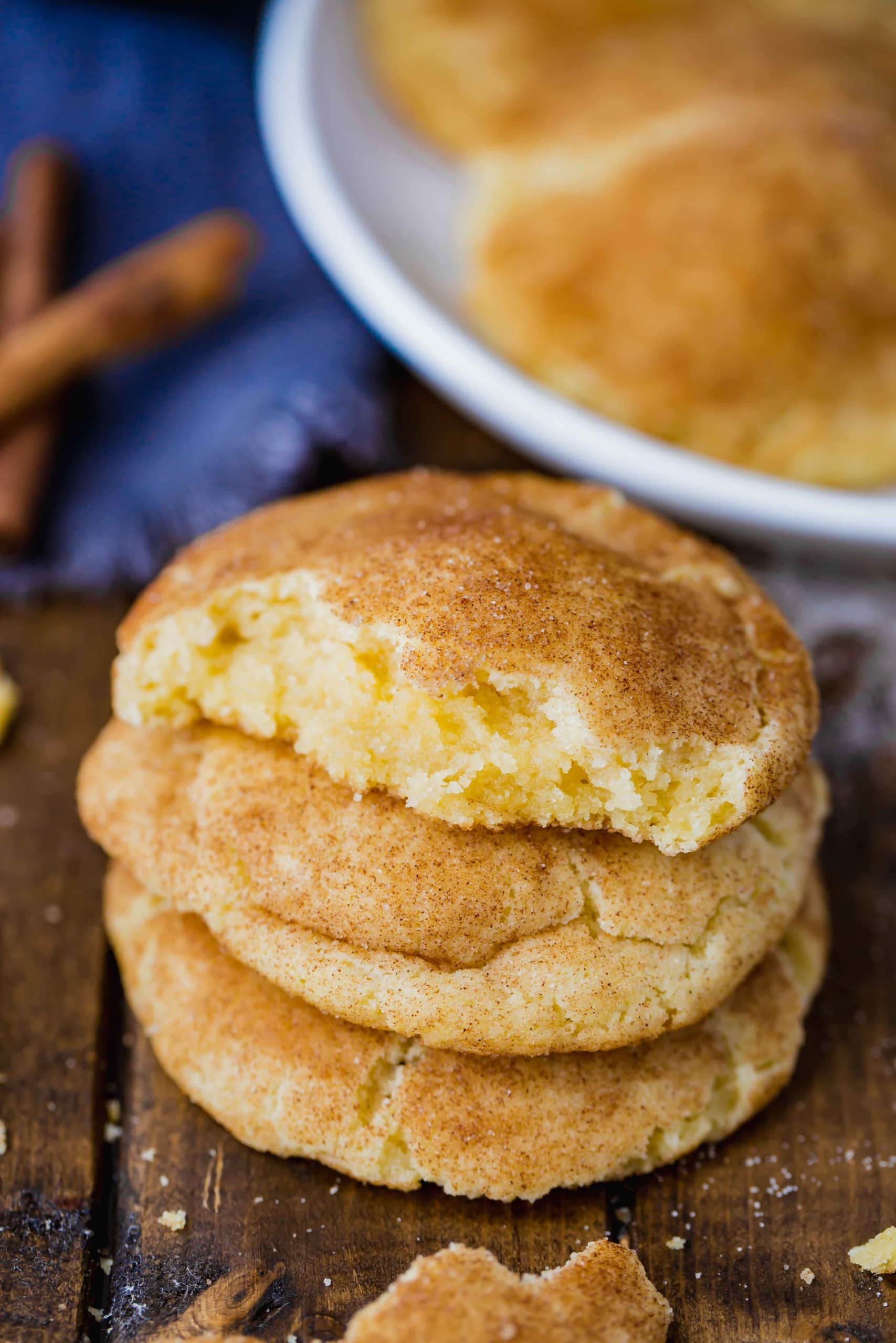 a photo of a stack of three soft and chewy snickerdoodle cookies with the top cookie broken in half.