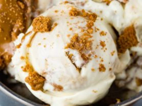 A photo of several scoops of Biscoff cookie butter homemade ice cream in a dark gray bowl with cookie crumbles all over the top.