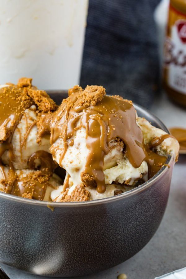 A photo of several scoops of Biscoff cookie butter homemade ice cream in a dark gray bowl with cookie crumbles and melted cookie butter all over the top.